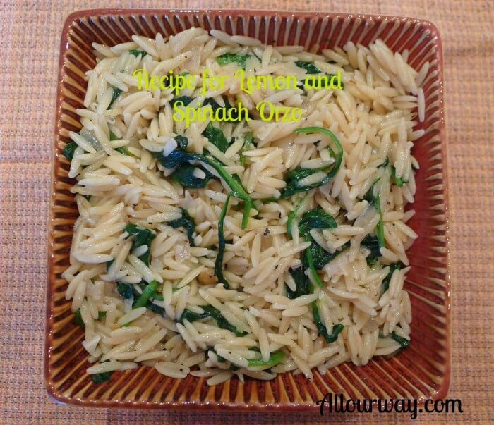 Lemon and spinach orzo pasta recipe resembles risotto in a square brown dish on top of a brown and orange dishtowel. @Allourway.com