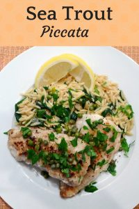 Sea Trout Piccata on a white plate with orzo spinach pasta, lemon wedges, capers, and green parsley.