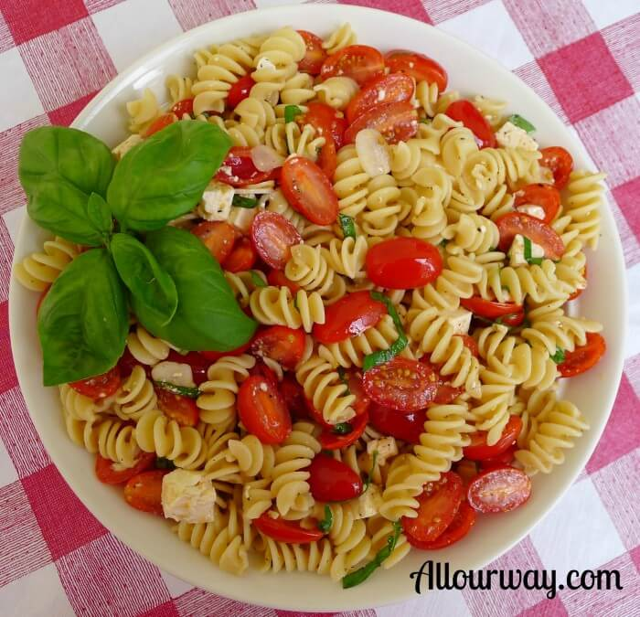 Rotini with Fresh Lemon, Grape Tomatoes and Basil in a white bowl on top of a red and white checkered tablecloth.