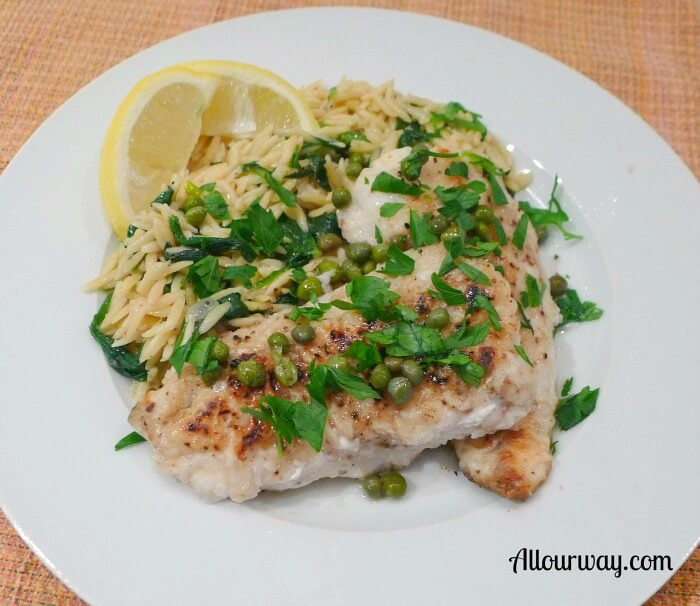 Nicely browned sea trout piccata with capers, green parsley, and lemon on a white plate.