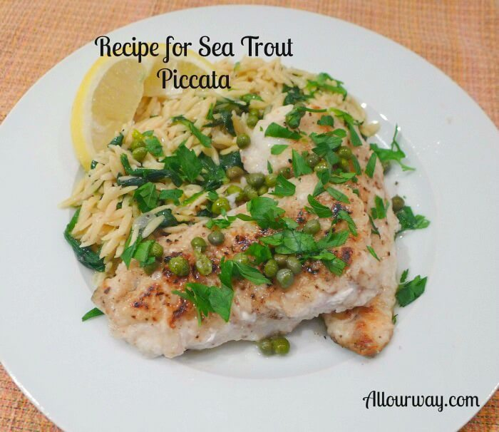 Baked sea trout piccata with lemon orzo pasta on a white plate with lemon wedges and parsley and capers over the fish.