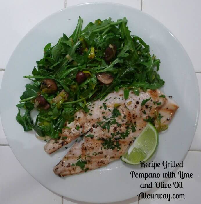 Gilled pompano with lime and olive oil on a white plate with a wedge of lime and a salad of arugula with mushrooms on the side.