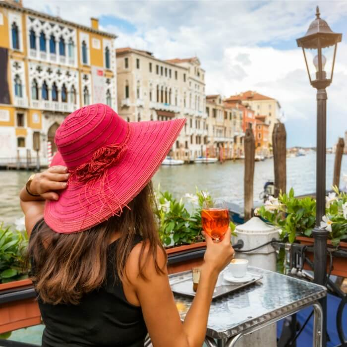 Lady with large rose hat sitting at an outdoor table looking at a canal in Italy