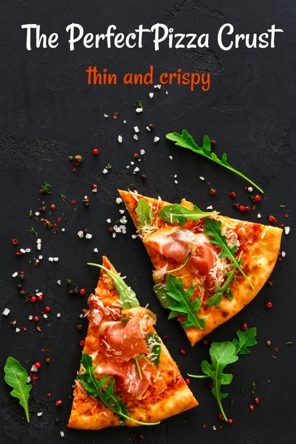 Two slices pizza on black background with hot pepper flakes around pizza and green arugula on top.