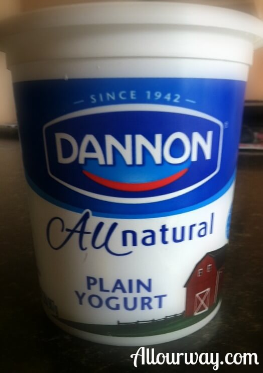 A closeup of a blue and white container of All Natural Dannon plain yogurt.