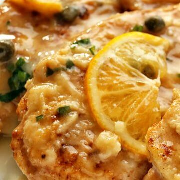 Close up golden brown chicken piccata on a platter with slices of lemon and capers over it.