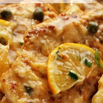 Slice of lemon and green caper buds cover the golden brown chicken piccata breasts.