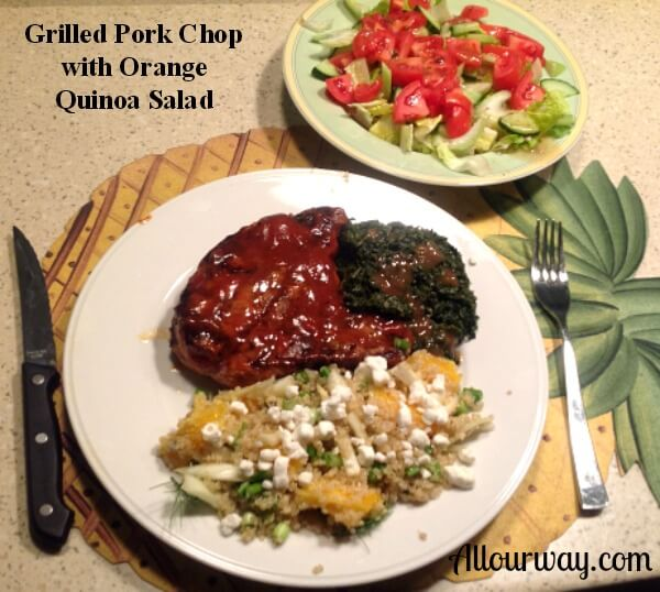 A table setting with grilled pork chop slathered with red sauce, sautèed spinach, orange quinoa salad, a small tossed salad with red diced tomatoes on top. A knife and fork are on either side of the plate.