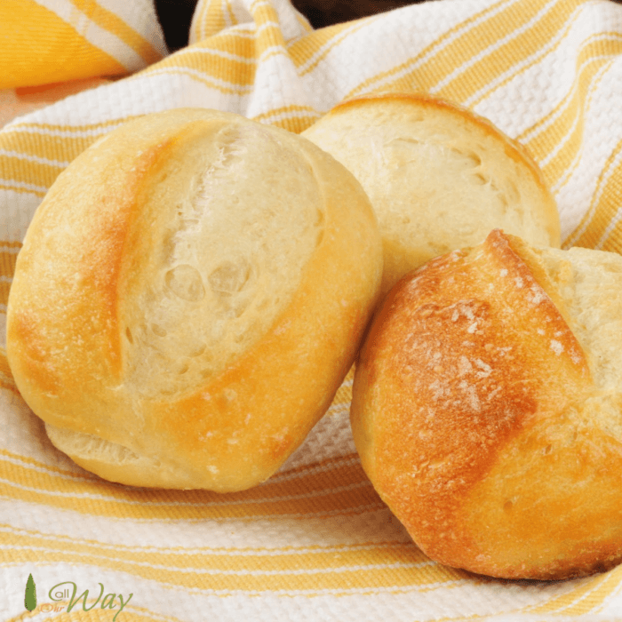 Yeast dinner rolls on top of yellow and white striped tea towels.