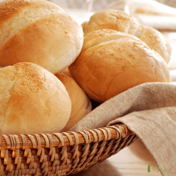 Close up of hard yeast rolls in a straw basket lined with ecru linen napkin