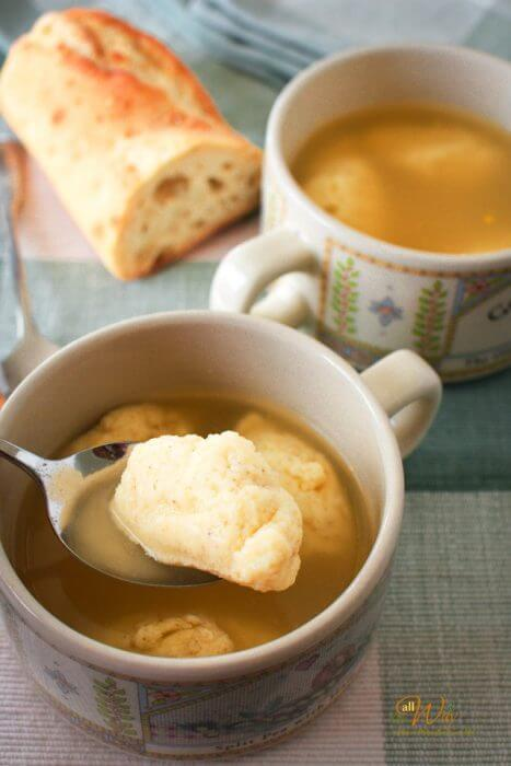 A closeup of a light gold dumpling on a spoon with the large cup of soup below the spoon. Another cup of soup is not the right side with a loaf of Italian bread all on green and white plaid placemat.