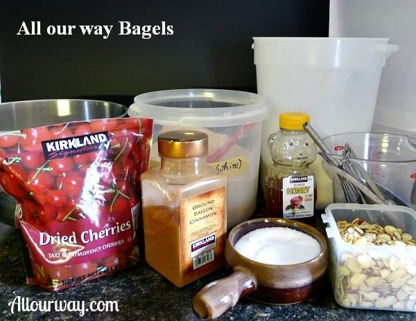 Homemade bagels ingredients lined up, dried cherrie, cinnamon, salt, almonds. honey, white whole wheat, all-purpose flour.