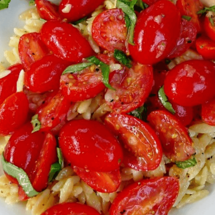 Close up of orzo pasta with marinated grape tomatoes over it and slivers of basil ribbons.