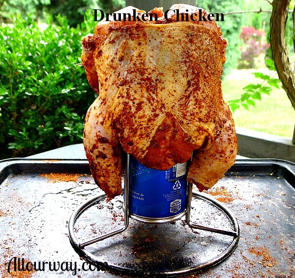 Seasoned chicken sitting on beer can on baking tray