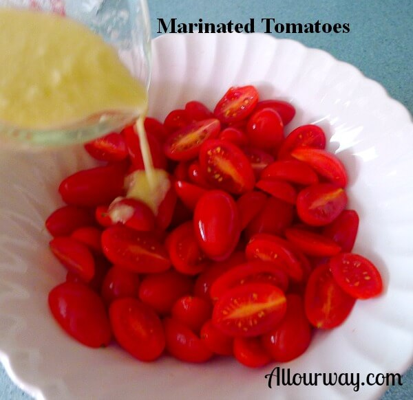 Red grape tomatoes in a white bowl with a vinegar and oil vinaigrette being poured on to marinate them.