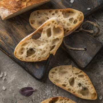 Loaf of Italian bread on a dark wood cutting board with slices of the bread on the board and counter.