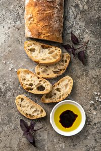 Sliced Italian loaf of bread on a cement counter with a bowl of olive oil and balsamic vinegar.