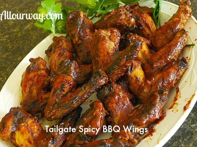 Rows of Spicy Bourbon Barbecued Chicken Wings on a white platter with green parsley on the top side.