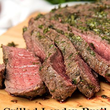 London broil steak sliced on a wooden cutting board.
