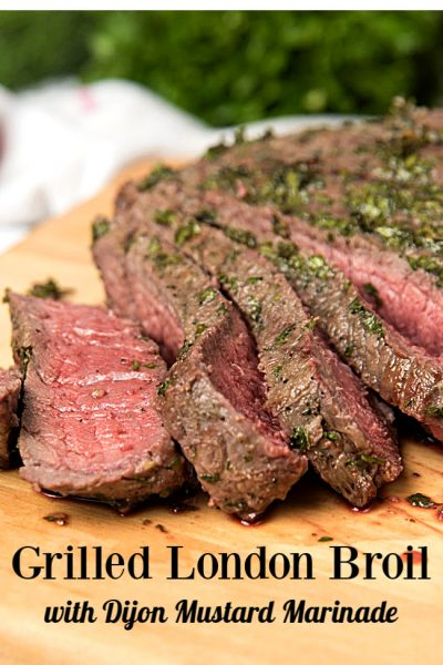 London broil steak sliced on a wooden cutting board.
