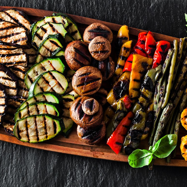 A platter of grilled vegetable slices, zucchini, mushrooms, peppers, asparagus, eggplant.