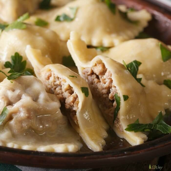 Homemade Italian Ravioli filled with meat and cheese closeup of cut ravioli sprinkled with green parsley.