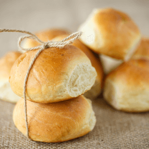 Potato sourdough buns stacked on a table with two tied with twine.