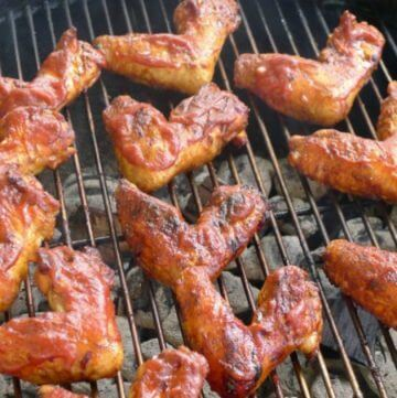 Close up of barbecued chicken on round grill grate cooking.