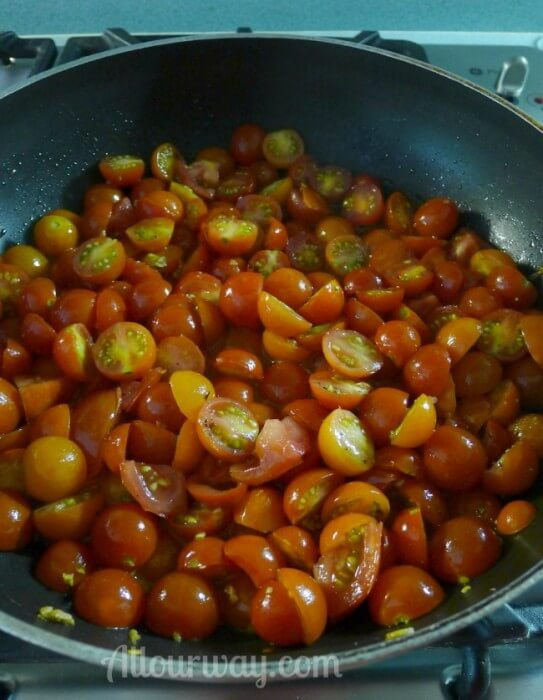 Cherry Tomatoes are halved and then put into the garlic olive oil at allourway.com
