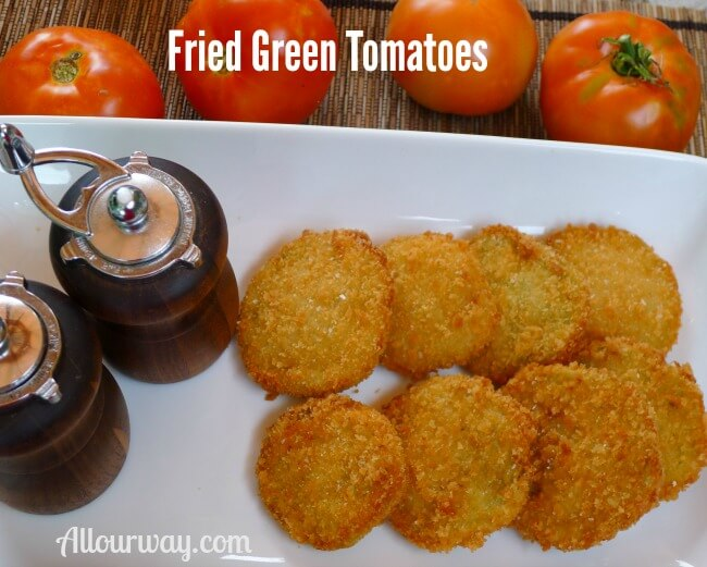 Crispy fried green tomatoes are breaded with panko crumbs are on a white plate with wooden salt and pepper grinder on the side and four red ripe tomatoes at the top.
