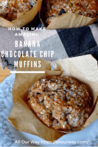 Banana Chocolate Chip muffin in brown parchment paper holder and more muffins in background.
