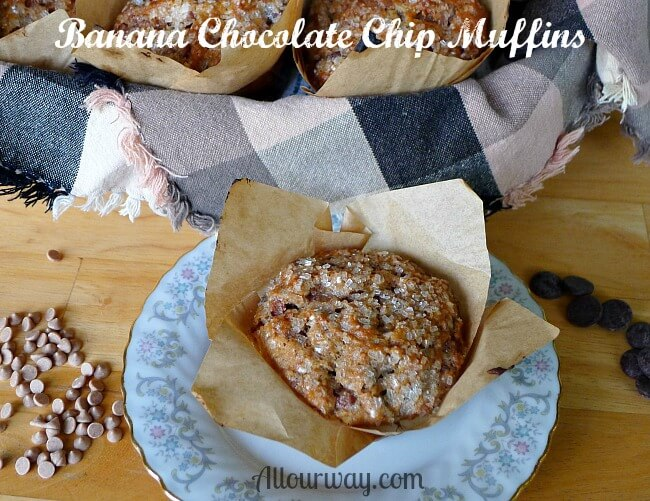 Banana Chocolate Chip Muffins with Cinnamon Chips along the side as well as chocolate chips on a wood board. Brown and black plaid cloth lined basket filled with muffins in brown parchment paper muffin cups.