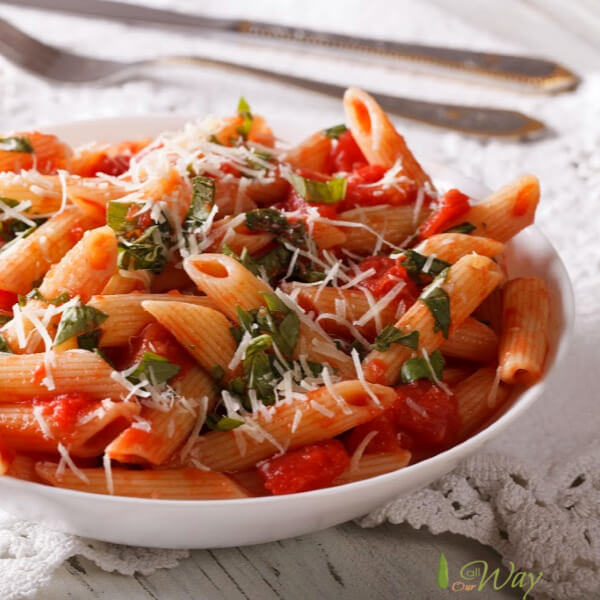 Penne pasta covered in red arrabbiata tomato sauce in a white bowl on top of a lace edged white cloth.