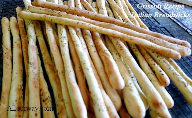 Grissini breadsticks on a black wire rack cooling. The crunchy Italian breadsticks are piled on top of each other.