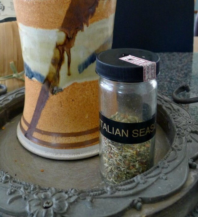 Closeup of a small jar of Grissini breadsticks spicy Italian seasoning for breadsticks. The jar is in front of an orange, white, black and brown pottery vase.