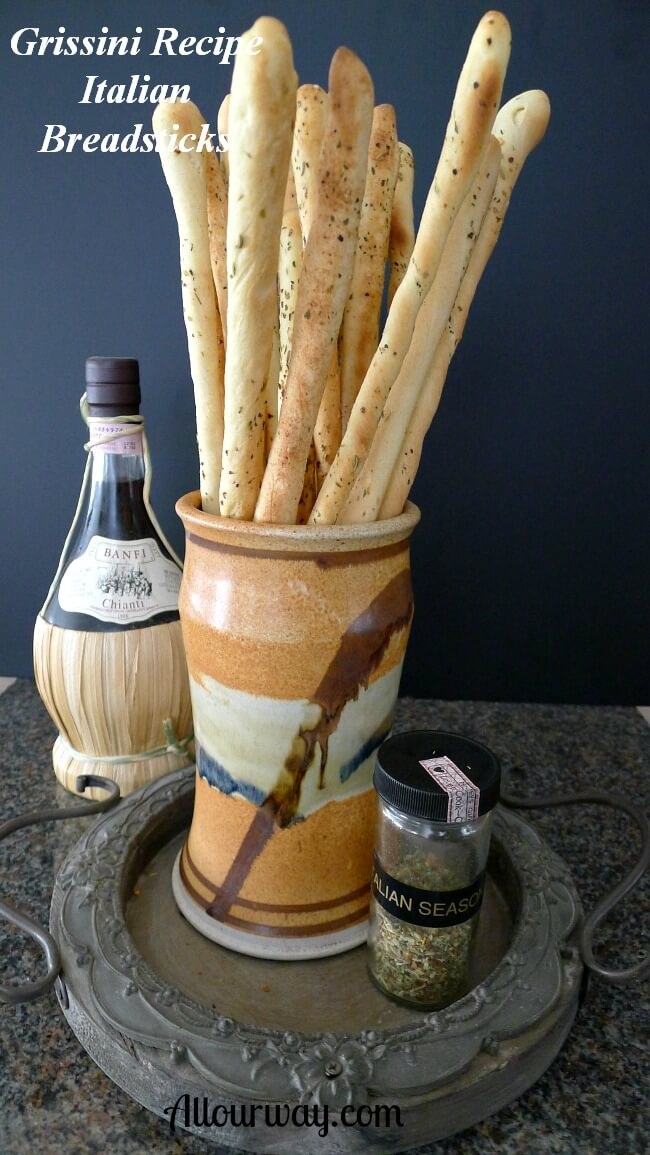 Grissini Breadsticks in an orange black and brown pottery vase. A bottle of straw-wrapped bottom chianti in the background with a shaker of Italian seasoning in the front of the tall Italian breadsticks.