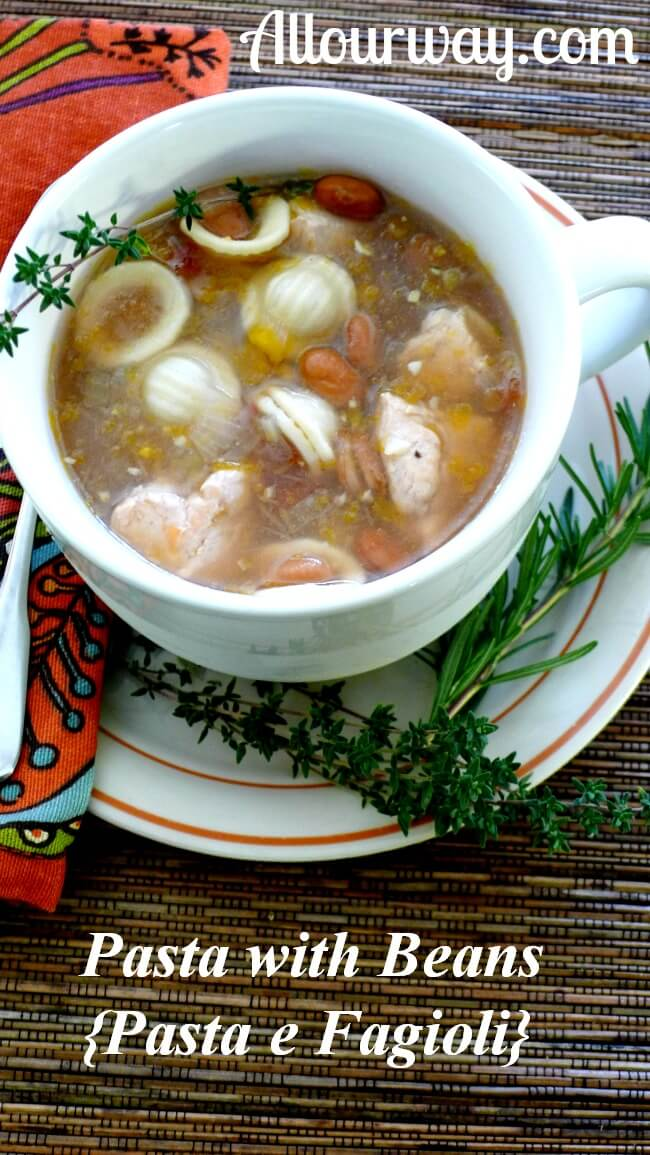 Pasta with beans {Pasta e fagioli} with thyme and rosemary in a large white soup mug with sprigs of rosemary and thyme on the side. A rust, turquoise, green napkin on the side all on top of bamboo placemat. @allourway.com