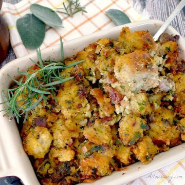 A casserole dish filled will Italian Sausage dressing with a sprig of rosemary on top and sage leaves on a white an orange checkered tea towel.