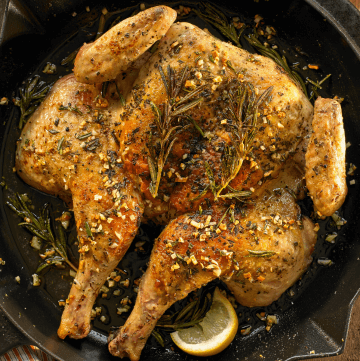 Chicken Under a Brick in a black cast iron skillet with lemons