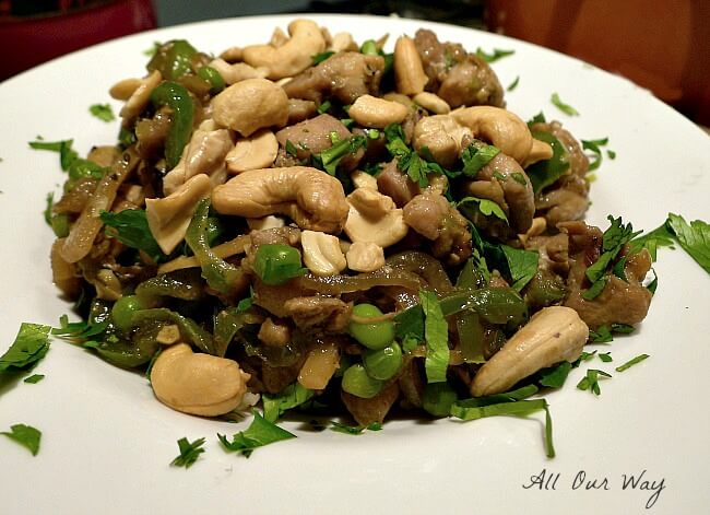 A side view of Chipotle Cashew chicken in a white bowl with peas, cashews, and cilantro on top.