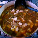 Hot and Sour Soup in a large pot with a black ladle and tofu cubes floating in clear broth.