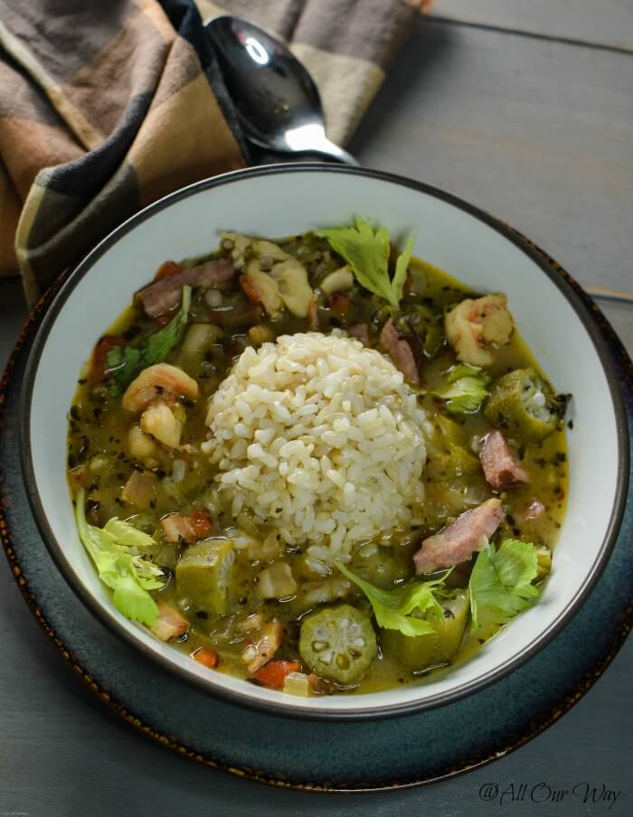 Louisiana shrimp gumbo in brown bowl with a scoop of rice. in the center on top of wood tabletop and brown and black check napkin.