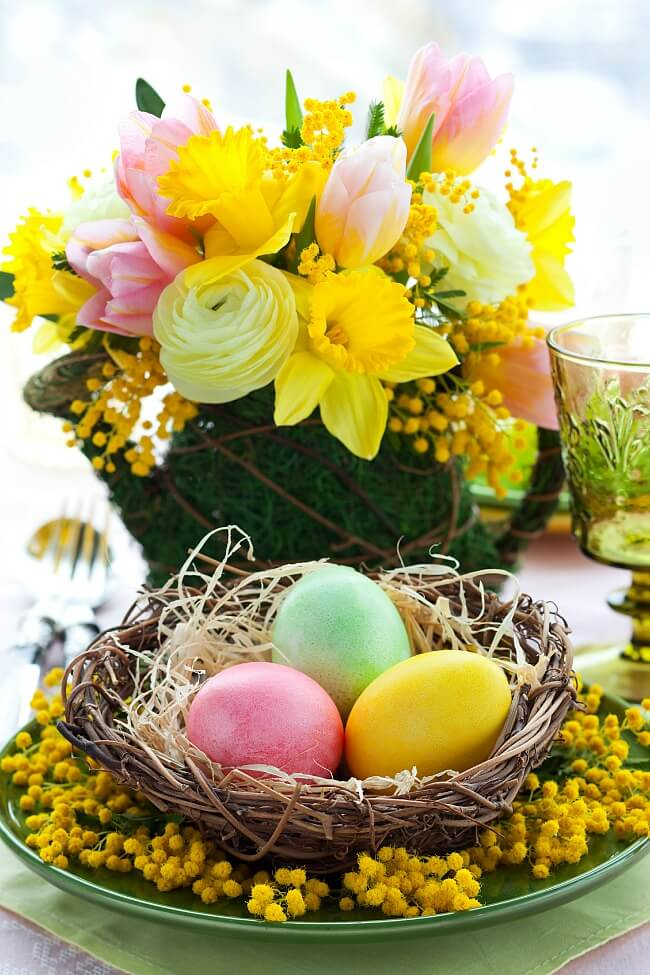Yellow daffodils and pink tulips in watering can vase and colored eggs in twig nest in front.
