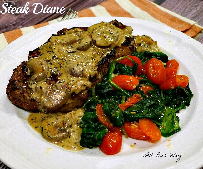 Steak Diane covered with mushroom gravy with green spinach and grape tomatoes on a white plate.