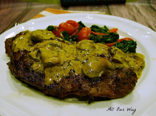Close up of Steak Diane on a white plate with green Spinach and red Grape Tomatoes Sauté @allourway.com