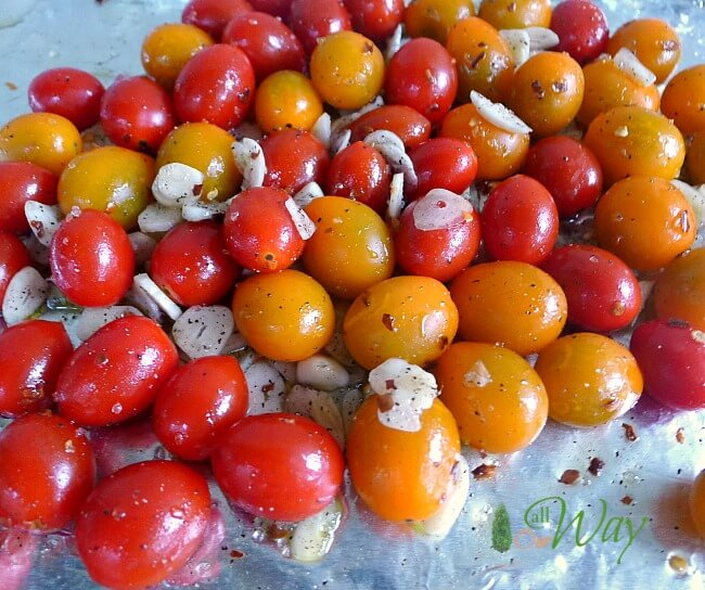 Grape tomatoes and sliced garlic with olive oil on foil lined cookie sheet ready to be roasted