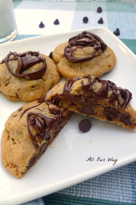 Sweet Salty Nutella Chocolate Chip Cookies with brown butter and sea salt on a white square plate with chips scattered around it all on a green and white plaid placemat. One cookie is split and half showing the nutella filling. @allourway.com