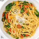 A white plate filled with pasta and a sauce of roasted grape tomatoes, garlic, and spinach.