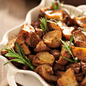 Golden brown quartered roasted potatoes in white scalloped edged casserole. Sprigs of rosemary with potatoes.