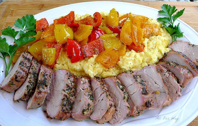 Grilled whole pork tenderloin sliced with colored peppers over Polenta on a white platter @allourway.com